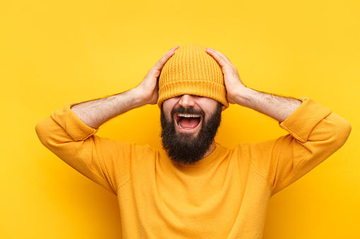Laughing bearded hipster in sweater covering eyes with hat standing on yellow.
