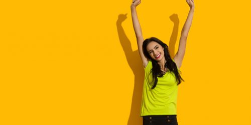 Beautiful young woman in lime green shirt and black shorts is holding arms raised and smiling. Three quarter length studio shot on yellow background.